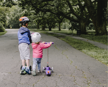 Two young children on scooters in the park