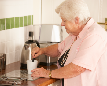 Woman making cup of tea in her house