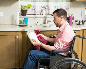 Man in wheelchair drying his dishes