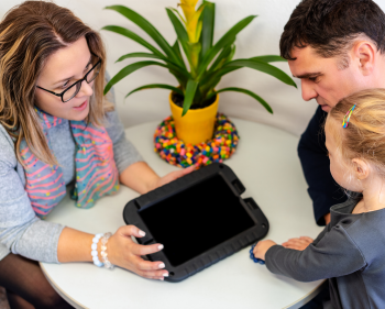 Woman showing ipad to dad and young child
