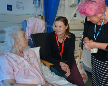 Two social workers talk with elderly patient on the ward