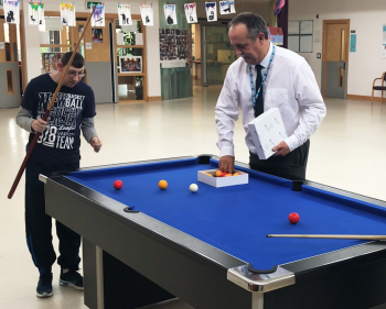 Staff playing snooker with visitor to Lisburn activity resource centre