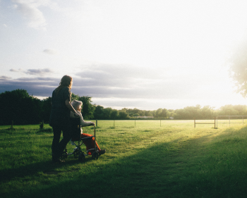 Older woman being wheeled along the grass by support worker