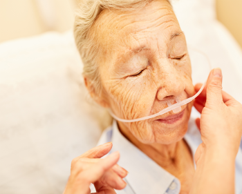 Elderly woman receiving oxygen therapy