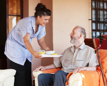 Health care worker bringing lunch to an elderly man in his own house
