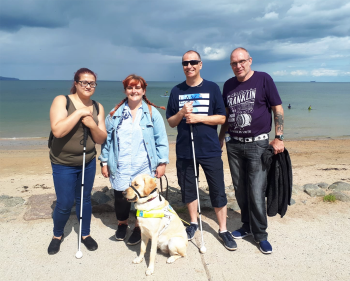 Four service users with guide dog on a beach walk