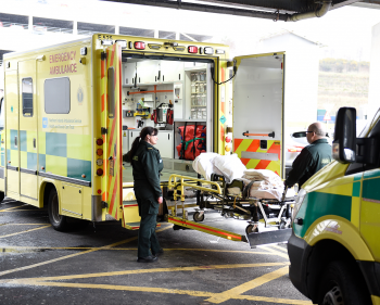 Stretcher being loaded onto ambulance by two paramedics